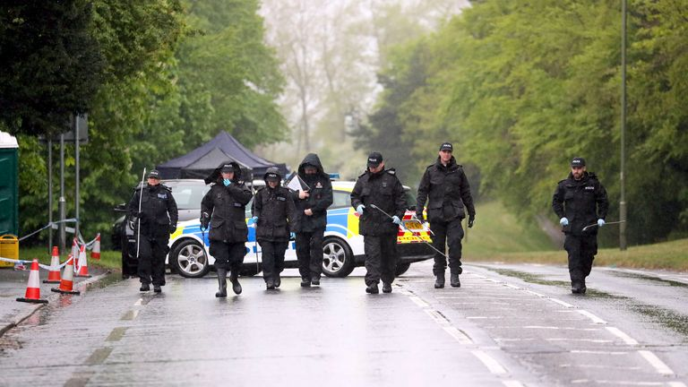 Officers from Surrey Police search for evidence on the A25 Bletchingley Road
