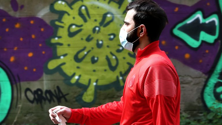 A man wearing a mask walks past coronavirus related graffiti in Edinburgh as the UK continues in lockdown to help curb the spread of the coronavirus