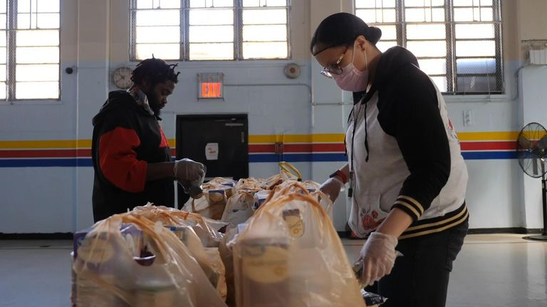 Two volunteers are seen preparing packages in the food bank.
