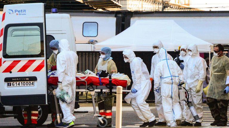 Paramedics load a coronavirus patient on to an ambulance at Bordeaux's train station