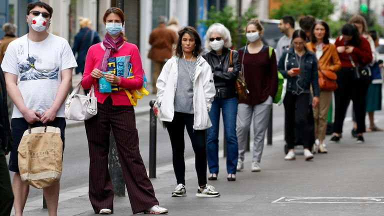 Mask-wearing shoppers queue outside a shop in Paris during lockdown measures