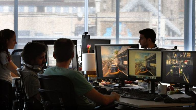 Employees of French video game developer Gameloft work on their computers during a visit to the company's studios of Barcelona with the Sagrada Familia in background on September 5, 2017. (Photo by LLUIS GENE / AFP) (Photo by LLUIS GENE/AFP via Getty Images)