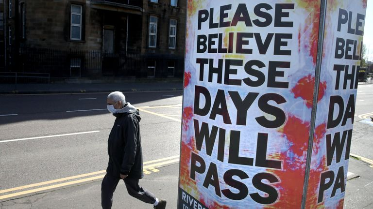 A person walks passed a billboard poster outside Glasgow Royal Infirmary as the UK continues in lockdown to help curb the spread of the coronavirus