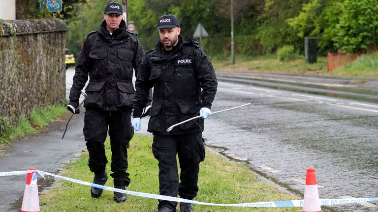 Officers from Surrey Police search for evidence near the home in Godstone where an 88-year-old man was found dead
