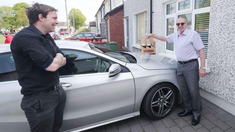 Richard Grainger observes social distancing when delivering pints