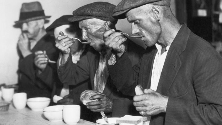 The Great Depression in the US: Men eating bread and soup in a breadline. Undated photograph