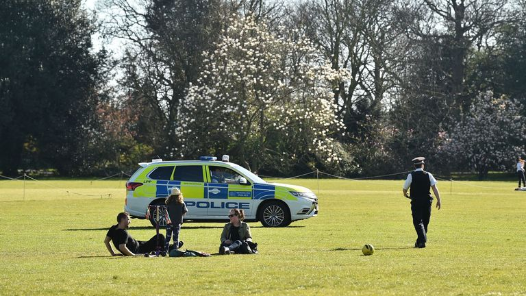 Police officers monitor as people take their daily exercise in Greenwich Park in south London on April 4, 2020, as life continues in the city during the novel coronavirus COVID-19 pandemic. - Britain on Friday reported a record 684 new COVID-19 deaths in its daily update, as the number of confirmed cases of coronavirus climbed by 4,450 on the previous 24 hours. (Photo by Glyn KIRK / AFP) (Photo by GLYN KIRK/AFP via Getty Images)