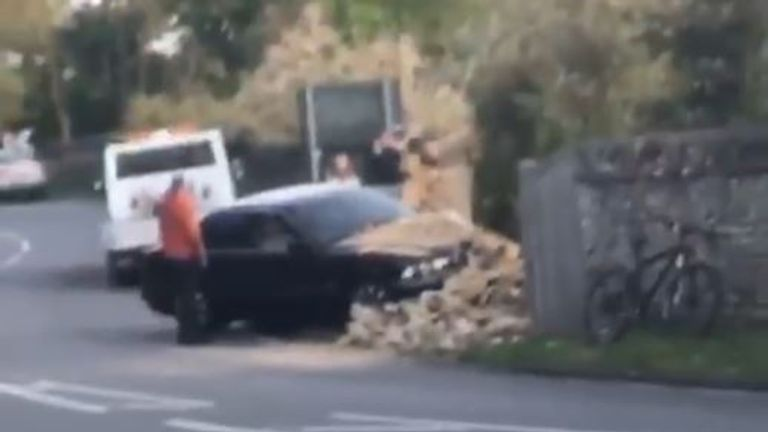A black car is seen being recovered after the crash