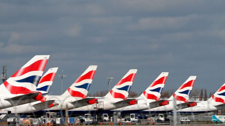 "This picture shows British Airways planes grounded at Heathrow's airport terminal 5, in west London, on March 16, 2020. - IAG, the owner of British Airways and Spanish carrier Iberia, said Monday it would slash the group's flight capacity by 75 percent during April and May owing to the coronavirus outbreak. ""For April and May, the Group plans to reduce capacity by at least 75 percent compared to the same period in 2019,"" it said in a statement. (Photo by Adrian DENNIS / AFP) (Photo by ADRIAN DEN"