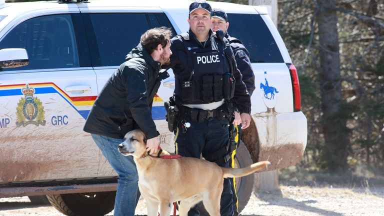 RCMP officer Cedric Landry releases a dog to a man at the checkpoint onto Portapique Beach Road after Gabriel Wortman, a suspected shooter, was taken into custody in Portapique, Nova Scotia, Canada April 19, 2020