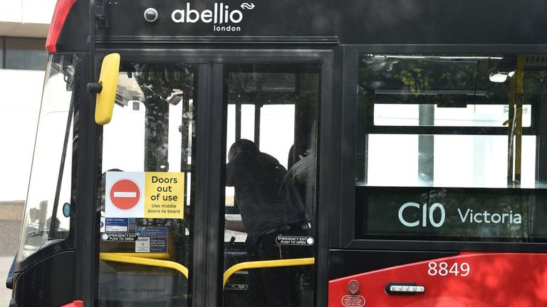 "A sign reading ""Doors out of use"" is pictured on the front doors of a London bus"