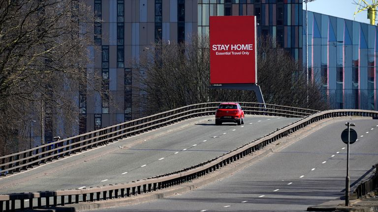 A giant television urges people to stay home on March 26 in Manchester