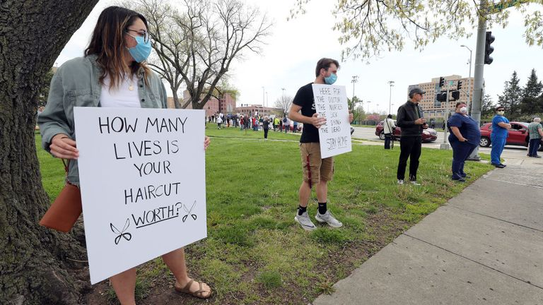 Counter-protesters McKinley Callin and Alec Overmann hold signs during a protest demanding that businesses be allowed to open up, and people allowed to go back to work, at the Country Club Plaza on April 20, 2020 in Kansas City, Missouri. The protest was part of a growing national movement against stay-at-home orders designed to slow the spread of the coronavirus. (Photo by Jamie Squire/Getty Images)