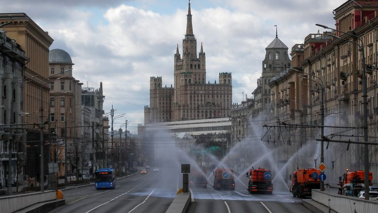 Vehicles spray disinfectant while sanitizing a road in Moscow