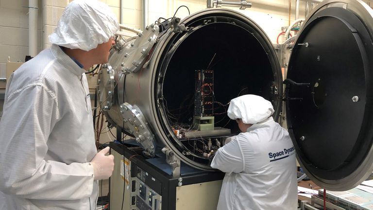 HARP Systems Engineer Ryan Martineau (left) and Thermal Vacuum Specialist Brittany Woytko configure HARP's spacecraft in a thermal vacuum chamber at the Space Dynamics Laboratory in Logan, Utah. Woytko is connecting several temperature sensors to the spacecraft to monitor the instrument during testing. Once the door is shut on the chamber, it loses its air and simulates the vacuum of space. The chamber also heats and cools the spacecraft through several cycles to simulate the extreme hot and col