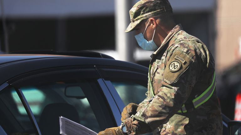 Members of the National Guard communicate with individuals at a newly opened Coronavirus testing site in Brooklyn on April 11, 2020 in the Brooklyn borough of New York City. According to John Hopkins University, the global death toll from COVID-19 has now reached 100,000 worldwide with many experts believing that the number is actually higher