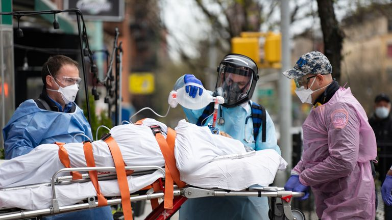 Fire Department of New York medical staff attend to an patient experiencing difficulty breathing outside an apartment