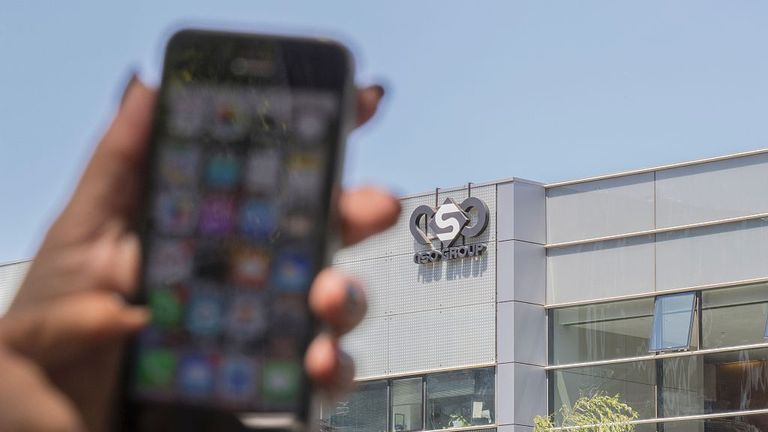 """An Israeli woman uses her iPhone in front of the building housing the Israeli NSO group, on August 28, 2016, in Herzliya, near Tel Aviv. Apple iPhone owners, earlier in the week, were urged to install a quickly released security update after a sophisticated attack on an Emirati dissident exposed vulnerabilities targeted by cyber arms dealers. Lookout and Citizen Lab worked with Apple on an iOS patch to defend against what was called """"Trident"""" because of its triad of attack methods, the researche"""