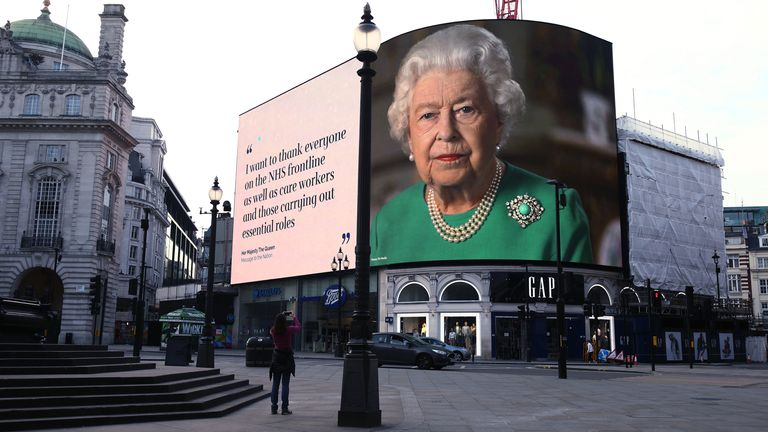 Quotes from the Queen's address are broadcast on the screens in an empty Piccadilly Circus