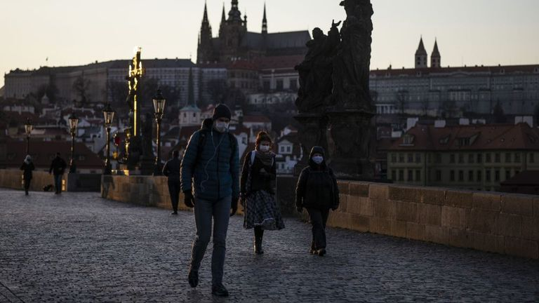 People wearing face masks walk in Prague
