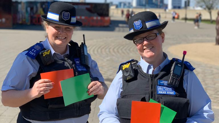 Two police officers are seen supporting the Red Green card scheme