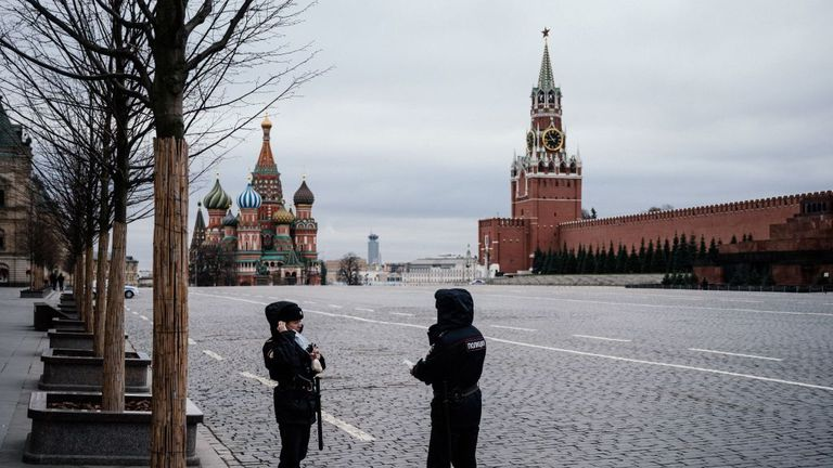 Police officers wearing face masks patrol on the empty Red square, with the St. Basil's Cathedral (L) and Kremlin's Spasskaya Tower (R) in the background, in Moscow on March 30, 2020, during a lockdown of the city to stop the spread of the epidemic COVID-19, caused by the novel coronavirus. - Moscow and its surrounding region imposed lockdowns March 30, 2020, that were being followed by other Russian regions in a bid to slow the spread of the coronavirus. The enforcement of the strict new rules,