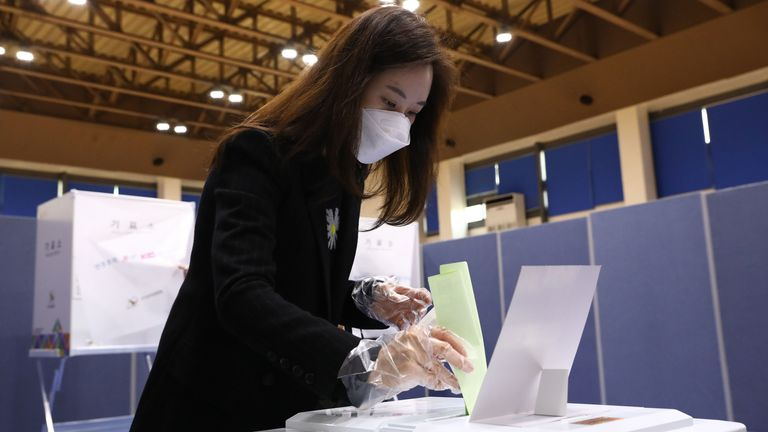 A woman wearing a mask and plastic gloves casts her vote at a polling station in Seoul