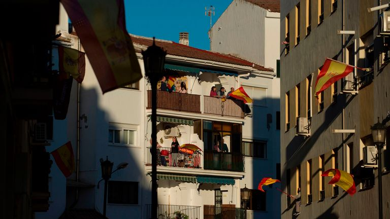 People applaud on their balconies to thank healthcare workers dealing with the COVID-19 coronavirus in Ronda on April 3, 2020