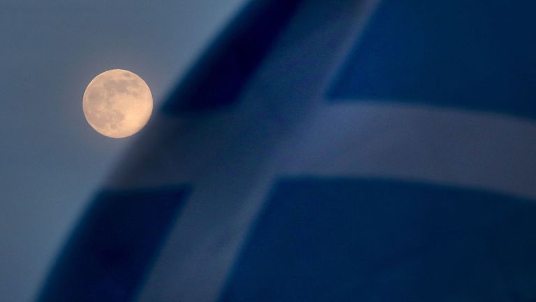 A pink supermoon is seen beside a Saltire flag in Falkirk