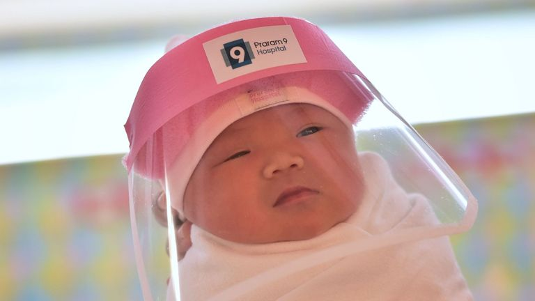 A newborn baby wearing a face shield, in an effort to halt the spread of the COVID-19 at Praram 9 Hospital in Bangkok