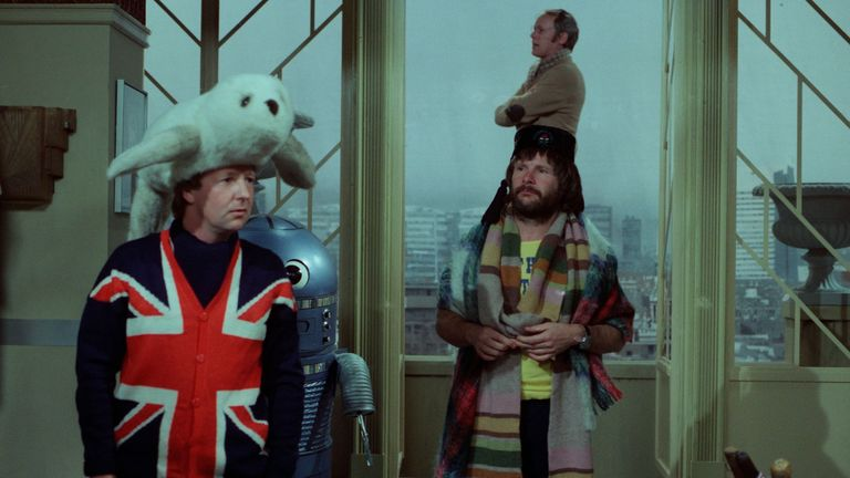 Tim Brooke-Taylor, seen in his familiar Union Flag waistcoat, in a scene from The Goodies, with Graeme Garden (rear) and Bill Oddie (right)