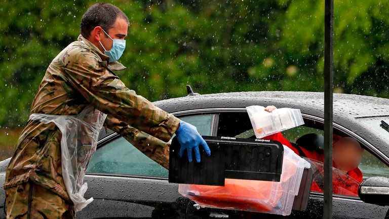 A soldier of the Royal Welsh regiment accepts the test of a key workerat a drive-in testing facility for the novel coronavirus COVID-19 in Salisbury, southwest England on April 30, 2020. - Britain's death toll from the coronavirus outbreak jumped to 26,097 on Wednesday -- the second-highest in Europe behind Italy and third-highest in the world -- as the government took into account fatalities outside hospital, including care homes, for the first time. (Photo by Adrian DENNIS / AFP) (Photo by ADRIAN DENNIS/AFP via Getty Images)