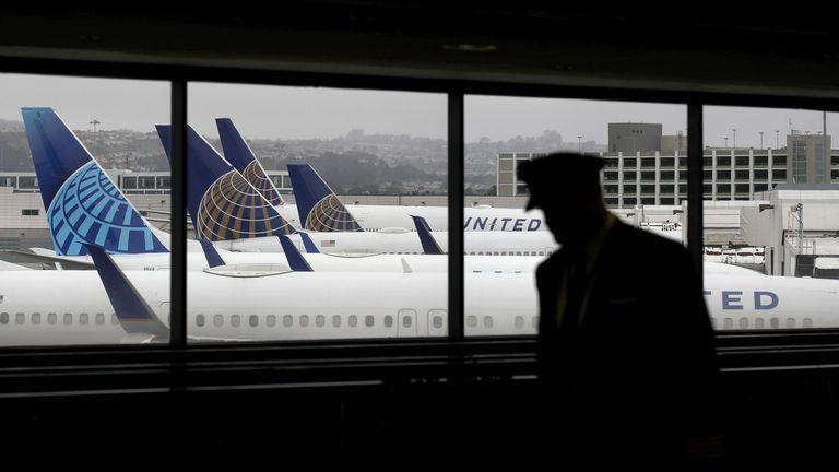 A pilot walks by United Airlines planes as they sit parked at gates at San Francisco International Airport on April 12, 2020