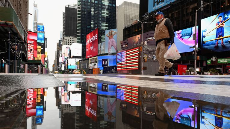 A man crosses the street at a nearly empty Time Square on April 09, 2020 in New York City.