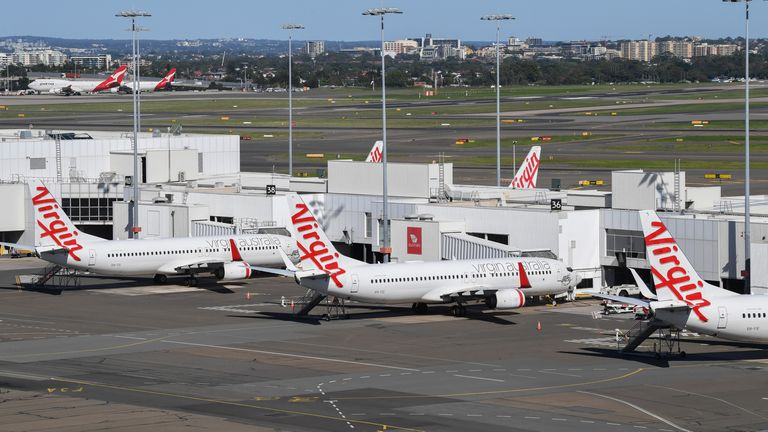 Virgin Australia planes sit at the domestic terminal at Sydney Airport with Qantas planes parked in the background on April 17, 2020 in Sydney, Australia.