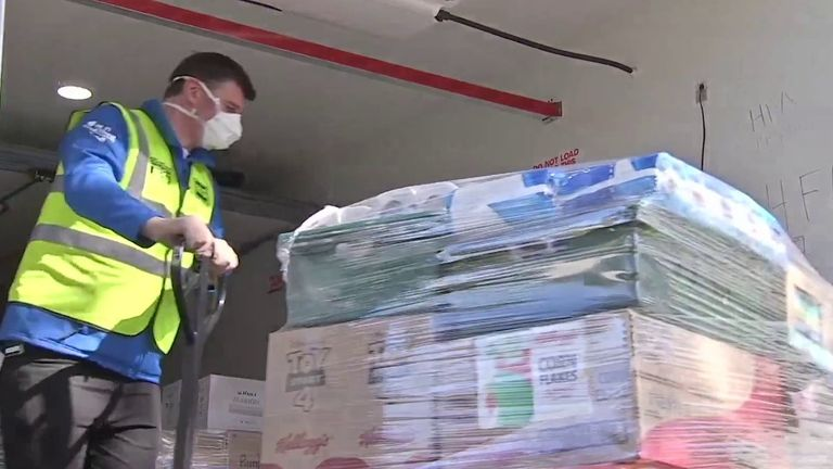 Worker helps to unload goods from lorry