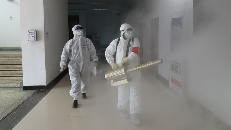 Volunteers in protective suits disinfect a residential compound in Wuhan