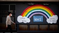 A man wearing a face mask walks past a rainbow graffiti in support of the NHS in Soho, central London, as the UK continues in lockdown to help curb the spread of the coronavirus.