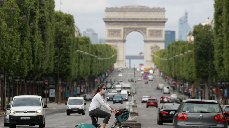 A cyclist wears a facemask as she crosses The Champs Elysees Avenue in Paris on May 4, 2020, on the forty-ninth day of a strict lockdown in France, in place to attempt to stop the spread of the new coronavirus (COVID-19). (Photo by Ludovic MARIN / AFP) (Photo by LUDOVIC MARIN/AFP via Getty Images)