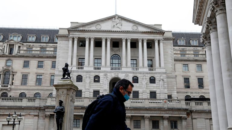 A man wearing protective face mask walks past the Bank of England in the City of London on March 30, 2020, as life in Britain continues during the nationwide lockdown to combat the novel coronavirus pandemic. - Life in locked-down Britain may not return to normal for six months or longer as it battles the coronavirus outbreak, a top health official warned on Sunday, as the death toll reached passed 1,200. (Photo by Tolga AKMEN / AFP) (Photo by TOLGA AKMEN/AFP via Getty Images)