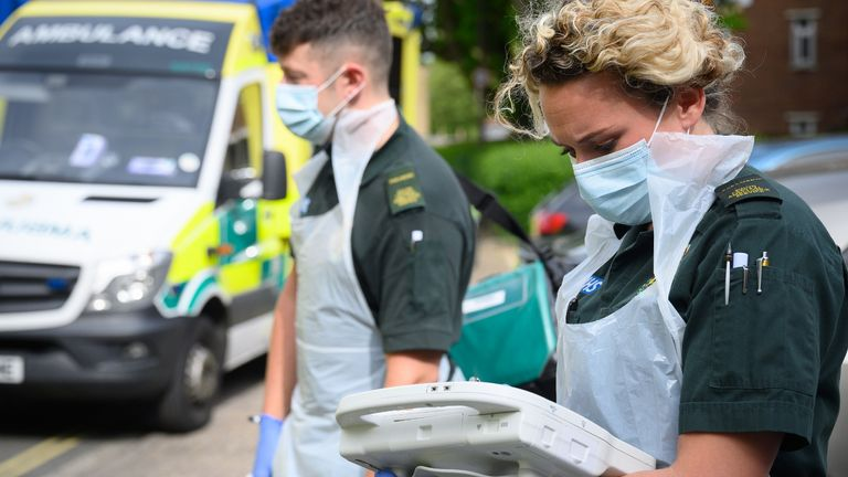 PORTSMOUTH, ENGLAND - MAY 05: An ambulance crew from the South Central Ambulance Service wear protective clothing as they complete the digital paperwork after responding to a false alarm call for a heart attack on May 05, 2020 in Portsmouth, England. Due to the risk of contamination to the air ambulance helicopters, patients have been transferred to the mainland using the hovercraft service since the beginning of May. As the list of recognised Covid-19 symptoms grows, paramedic crews like those with the South Central Ambulance Service are forced to treat every patient as being a potential case, often requiring specialised personal protective equipment (PPE). Paramedics now routinely don what the NHS refers to as Level 2 PPE, like face masks and disposable aprons. Cases with patients potentially needing airway procedures require Level 3 PPE, such as full-face visors and long-sleeved surgical gowns. While the infection rate is falling, and government officials are discussing ways to relax the country's quarantine measures, Covid-19 still creates everyday risks for paramedics and other first responders. (Photo by Leon Neal - Pool/Getty Images)