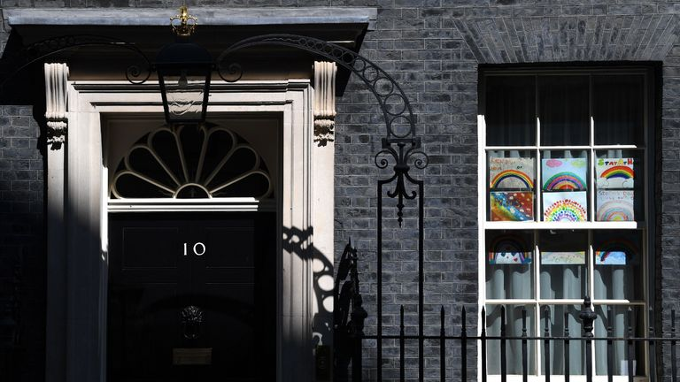 """Posters of rainbows, being used as symbols of hope during the COVID-19 pandemic are seen in the windows on 10 downing Street, on April 26, 2020, the day Britain's prime minister Boris Johnson is expected to return to the capital, during the national lockdown due to the novel coronavirus COVID-19 pandemic. - Britain's prime minister Boris Johnson will return to work at the start of this week, according to reports Sunday just hours after it was announced that the UK's coronavirus death toll had passed the """"tragic"""" milestone of 20,000. (Photo by DANIEL LEAL-OLIVAS / AFP) (Photo by DANIEL LEAL-OLIVAS/AFP via Getty Images)"""