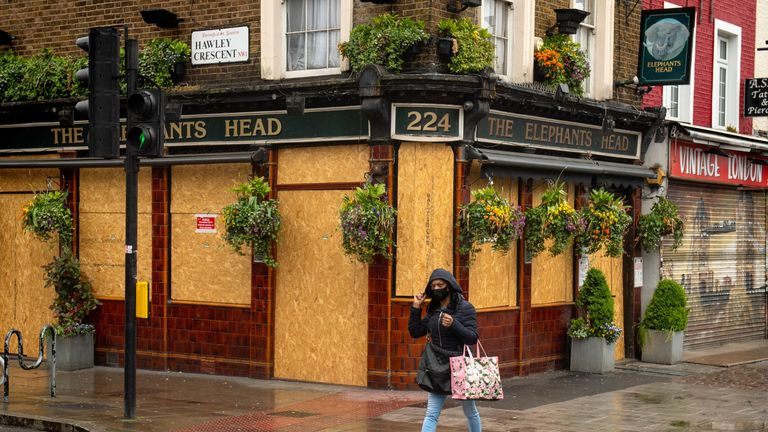 A woman walks past a boarded up pub in north London, as the UK continues in lockdown to help curb the spread of the coronavirus.