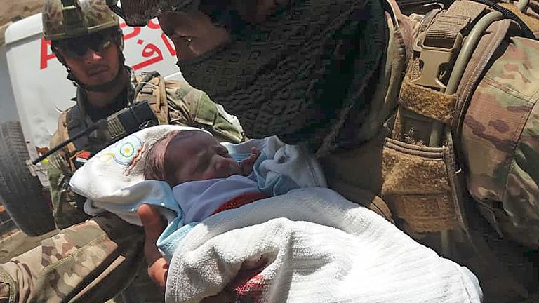 TOPSHOT - An Afghan security personnel carries a newborn baby from a hospital, at the site of an attack in Kabul on May 12, 2020. - Gunmen stormed a hospital on May 12 in an ongoing attack in the Afghan capital Kabul, a government official and a fleeing doctor said. (Photo by STR / AFP) (Photo by STR/AFP via Getty Images)