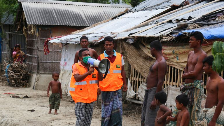 A Cyclone Preparedness Programme (CPP) volunteer uses a megaphone to urge residents to evacuate to shelters ahead of the expected landfall of cyclone Amphan in Khulna on May 19, 2020. - India and Bangladesh began evacuating more than two million people May 18 as a cyclone barrelled towards their coasts, with officials racing to ready extra shelters amid fears of coronavirus contagion in cramped refuges. (Photo by Kazi Shanto / AFP) (Photo by KAZI SHANTO/AFP via Getty Images)
