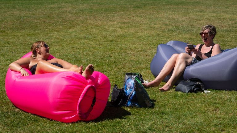 Two women sunbathe as people enjoy the hot weather in Greenwich Park, London, flocking to parks and beaches with lockdown measures eased.