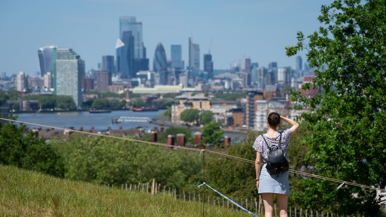 A woman looks out at the view of the London skyline as people enjoy the hot weather in Greenwich Park, London, flocking to parks and beaches with lockdown measures eased.