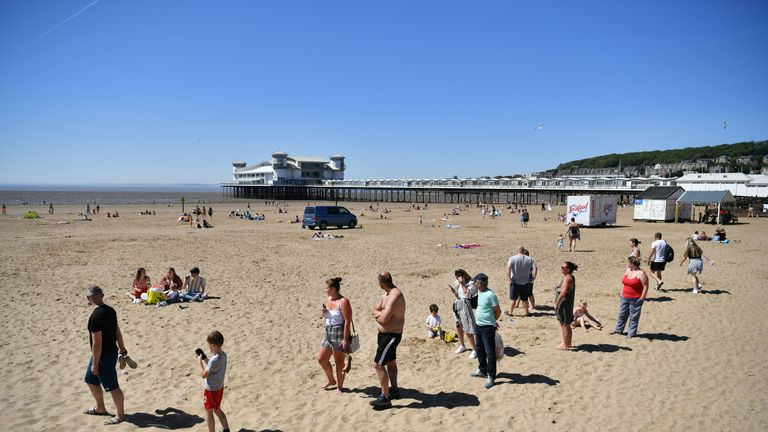 Sunbathers social distancing as they queue for ice cream as they enjoy the hot weather at Weston-super-Mare, as people flock to parks and beaches with lockdown measures eased.