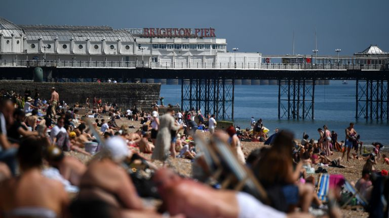 People enjoy the sunshine on the beach in Brighton, on the south coast of England on May 20, 2020, the hottest day of the year so far. - England's official coronavirus death toll rose to 25,079, after a further 166 people who tested positive for the Coronavirus (Covid-19) are reported to have died in hospitals. (Photo by Ben STANSALL / AFP) (Photo by BEN STANSALL/AFP via Getty Images)