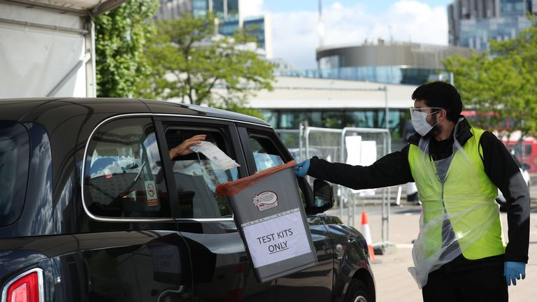 A customer throws a completed self-test sample into a container, at a Covid-19 drive-through test centre in Greenwich, London.